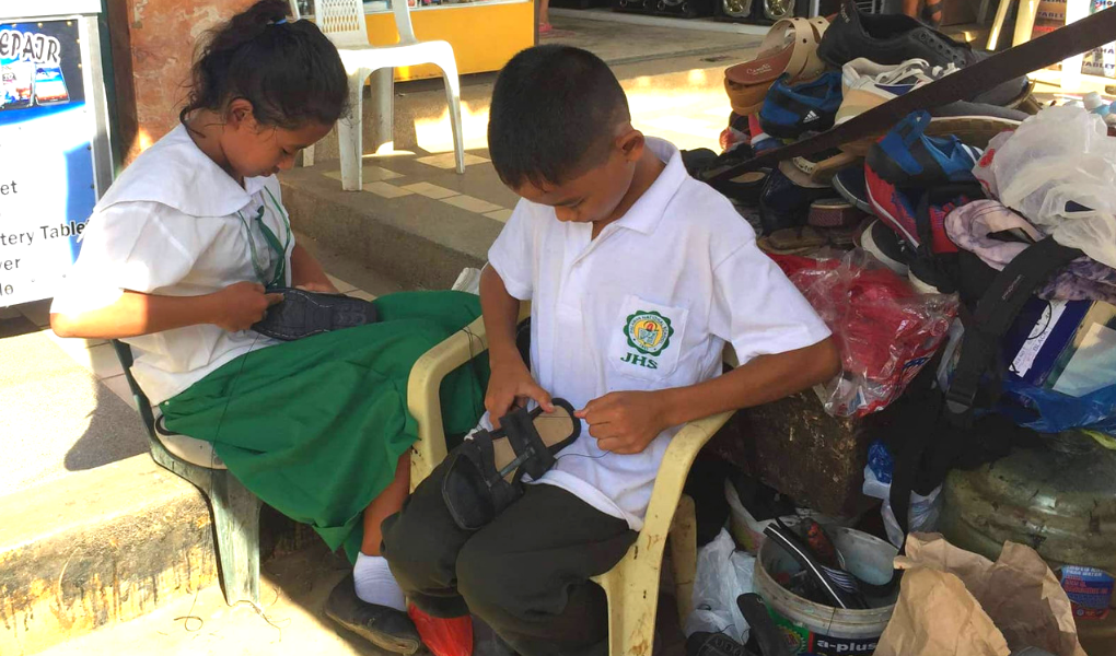 The siblings Emmanuelita and Meco Borbon, 13 and 12 years old respectively, spent the afternoon of their first day of school in the shoe repair stall of their family friend, Ruel, in Valencia Street, Puerto Princesa City. Photo by John Dale Arellano / Palawan Daily News