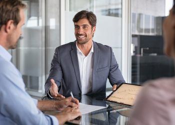 Confident financial agent showing growth graph to couple. Mid couple meeting financial advisor for investment. Business people discussing the charts and graphs showing the results of their successful teamwork.