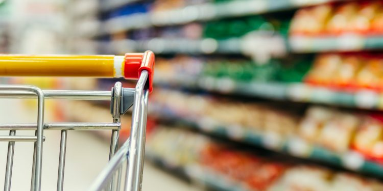 Shopping cart in supermarket. Part of shopping trolley in supermarket aisle. Blurred shelves in grocery store and trolley. Copy space for text or design.